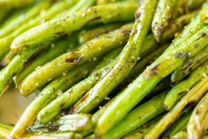 A close up shot of grilled green beans with some charring from the grill.