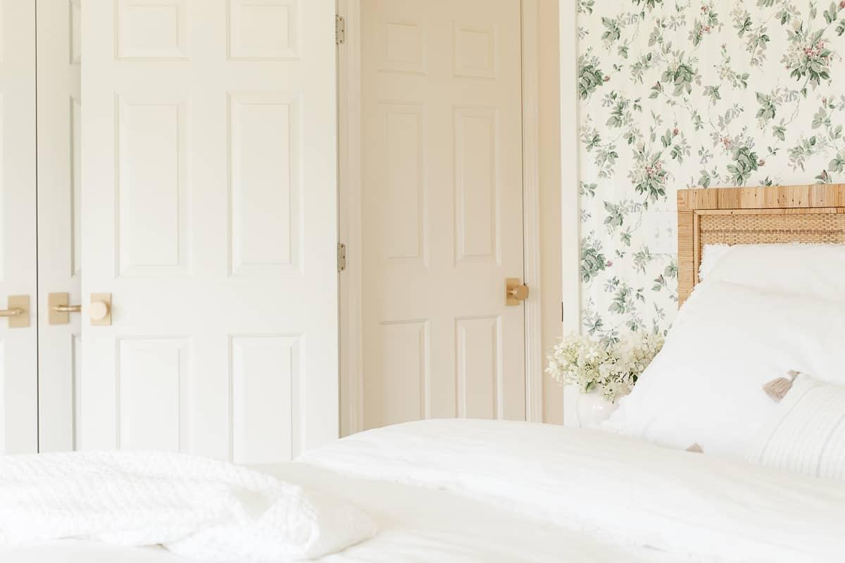 bedroom with wallpaper and modern satin brass door knobs