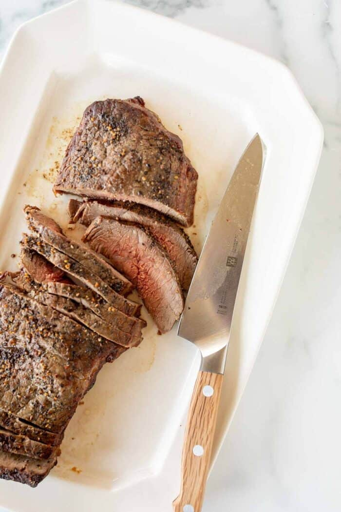 A large steak, cooked medium rare and cut into slices on a white platter, knife to the side.