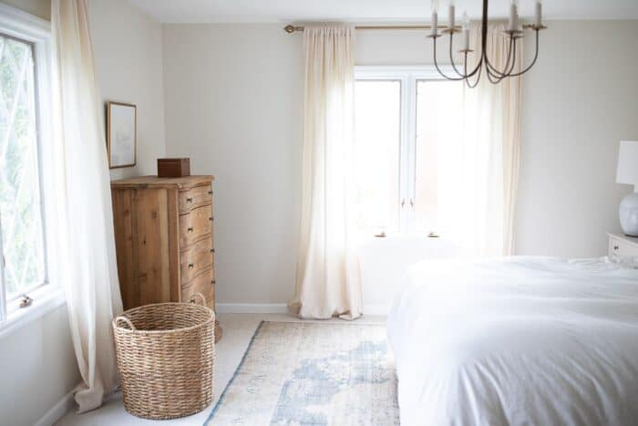 A white bedroom with a wooden dresser and the right size rug for a king bed.