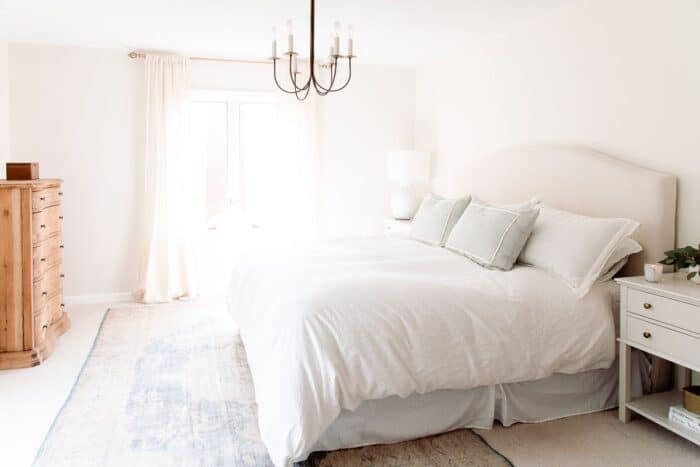A white bedroom with a large vintage rug under a king sized bed.