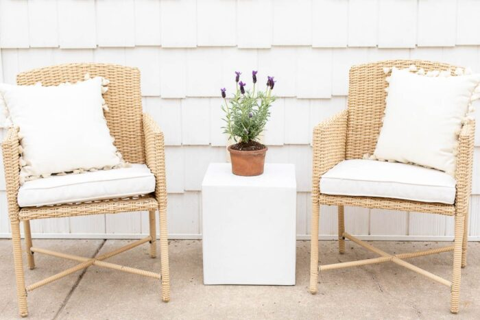 Two rattan chairs and a small square garden stool in between.
