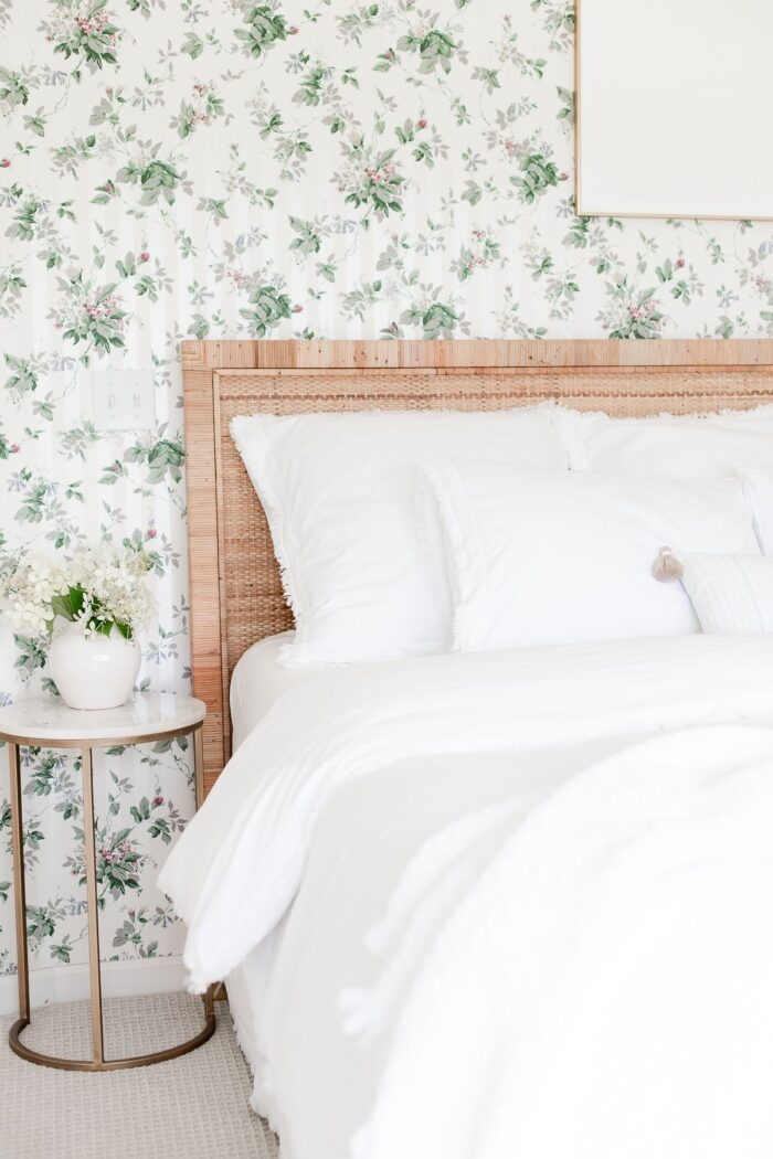 A bedroom with floral wallpaper, a rattan headboard, white bedding and a gold and marble side table.