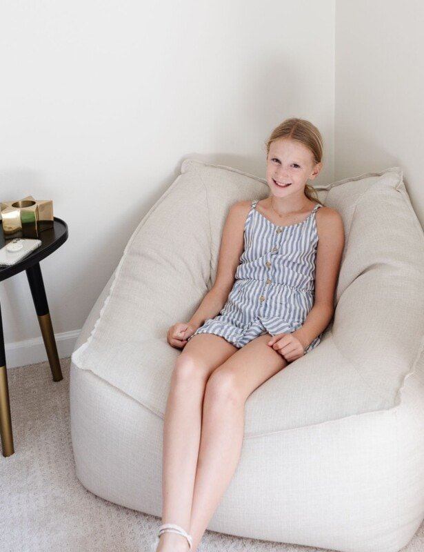 A young girl sitting on a Pottery Barn bean bag chair.