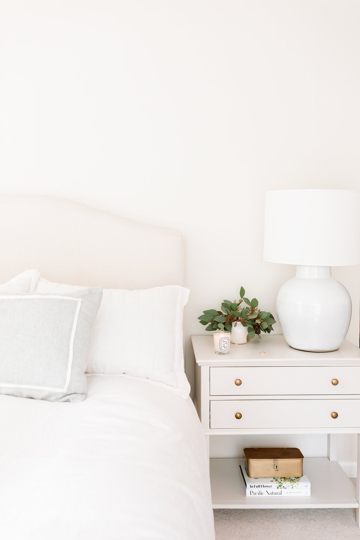 neutral bed and neutral nightstand at approximately the same bedside table height.