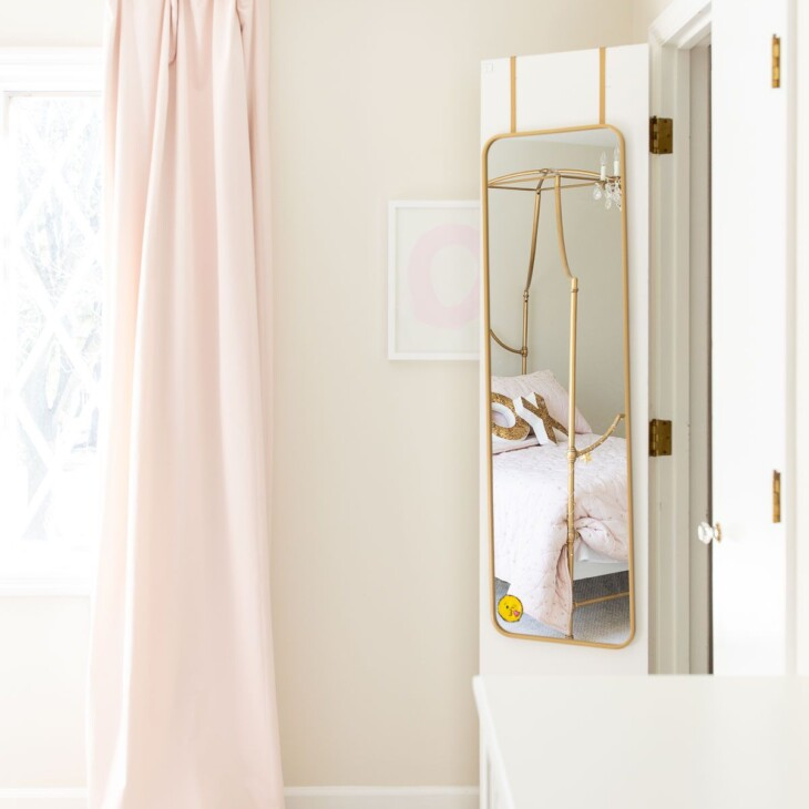 A girl's bedroom with pink blackout curtains and a mirror hanging on a closet door.