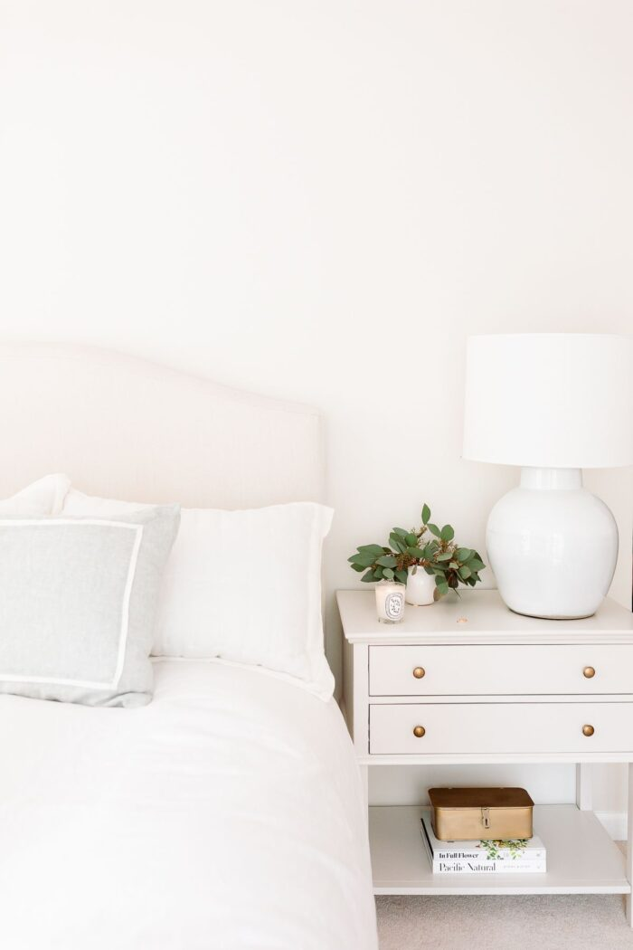 A cream bedroom with cream bed and greige nightstand