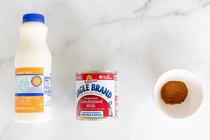 Heavy whipping cream, condensed milk and a bowl of cinnamon laid out on a marble surface.