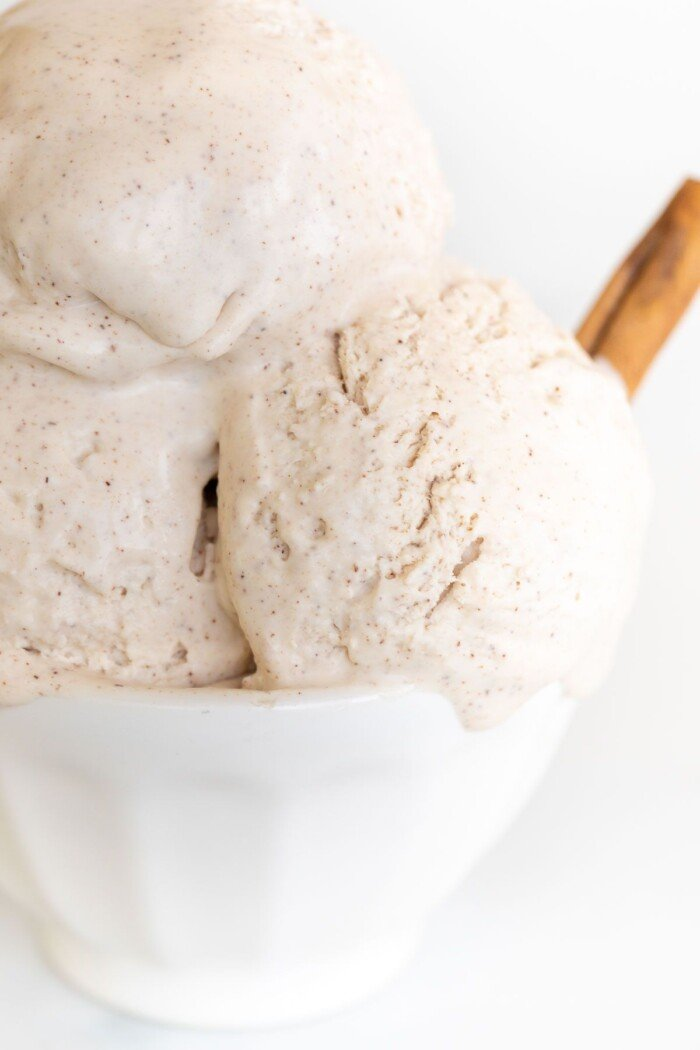 A white bowl full of homemade cinnamon ice cream with a cinnamon stick as garnish on the side