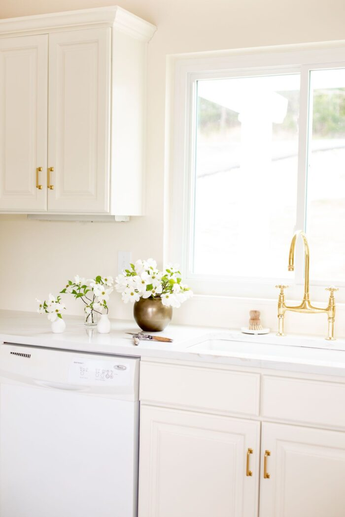 A white quartz countertop with an eased countertop edge, brass faucet on the sink in a cream kitchen.