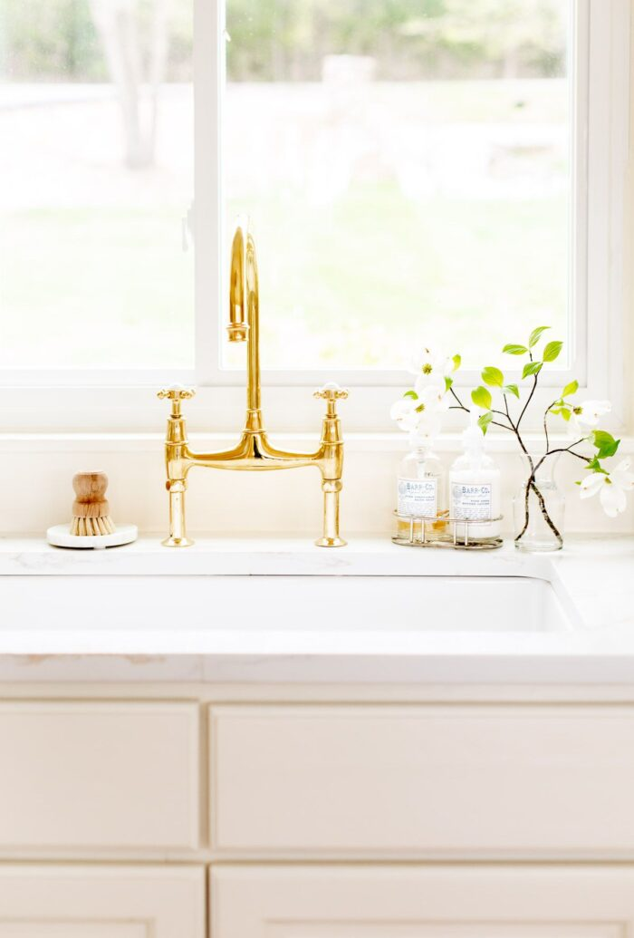 A white quartz countertop with an eased countertop edge, brass faucet on the sink.