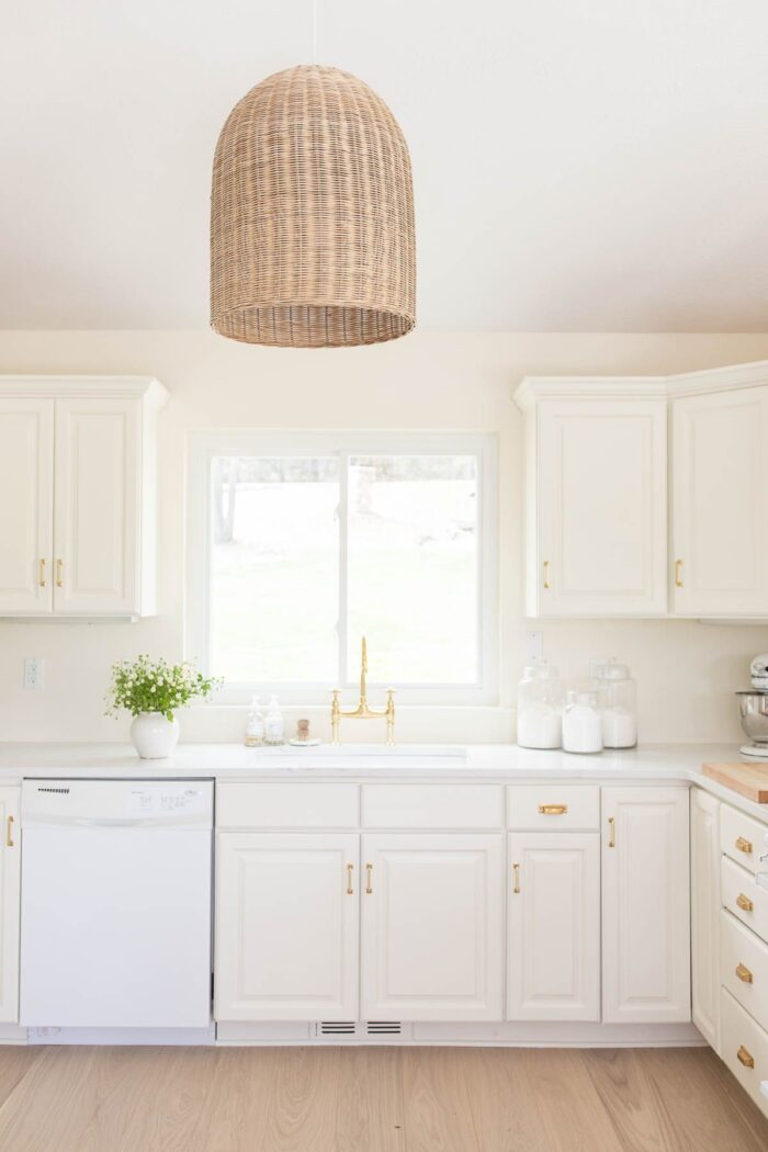 A cream painted kitchen with a basket light fixture and quartz countertops.