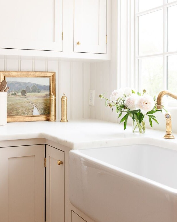 A cream colored kitchen with a marble eased edge countertop.