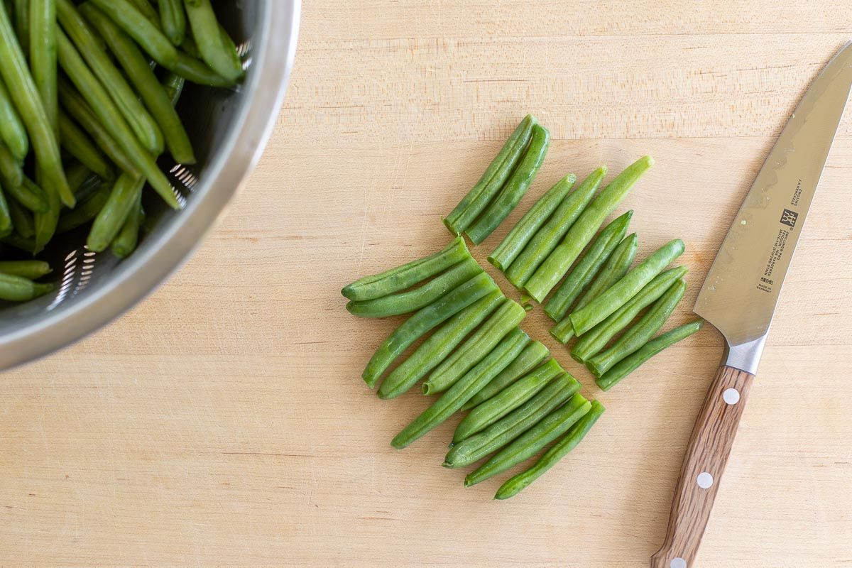 A wooden surface with sliced green beans and a knife to the right.