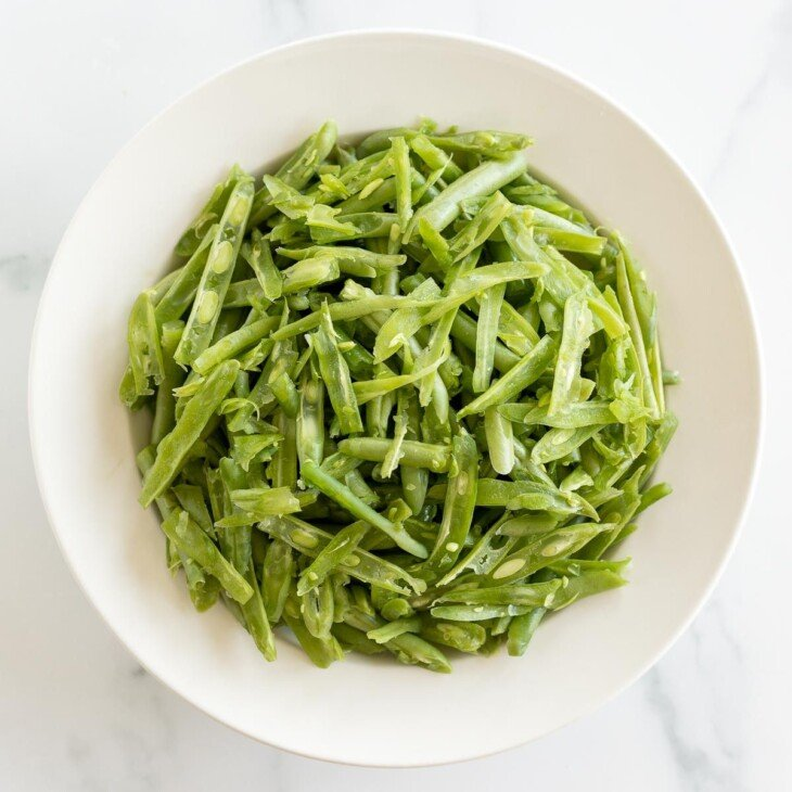 A white bowl on a marble surface, filled with French green beans.