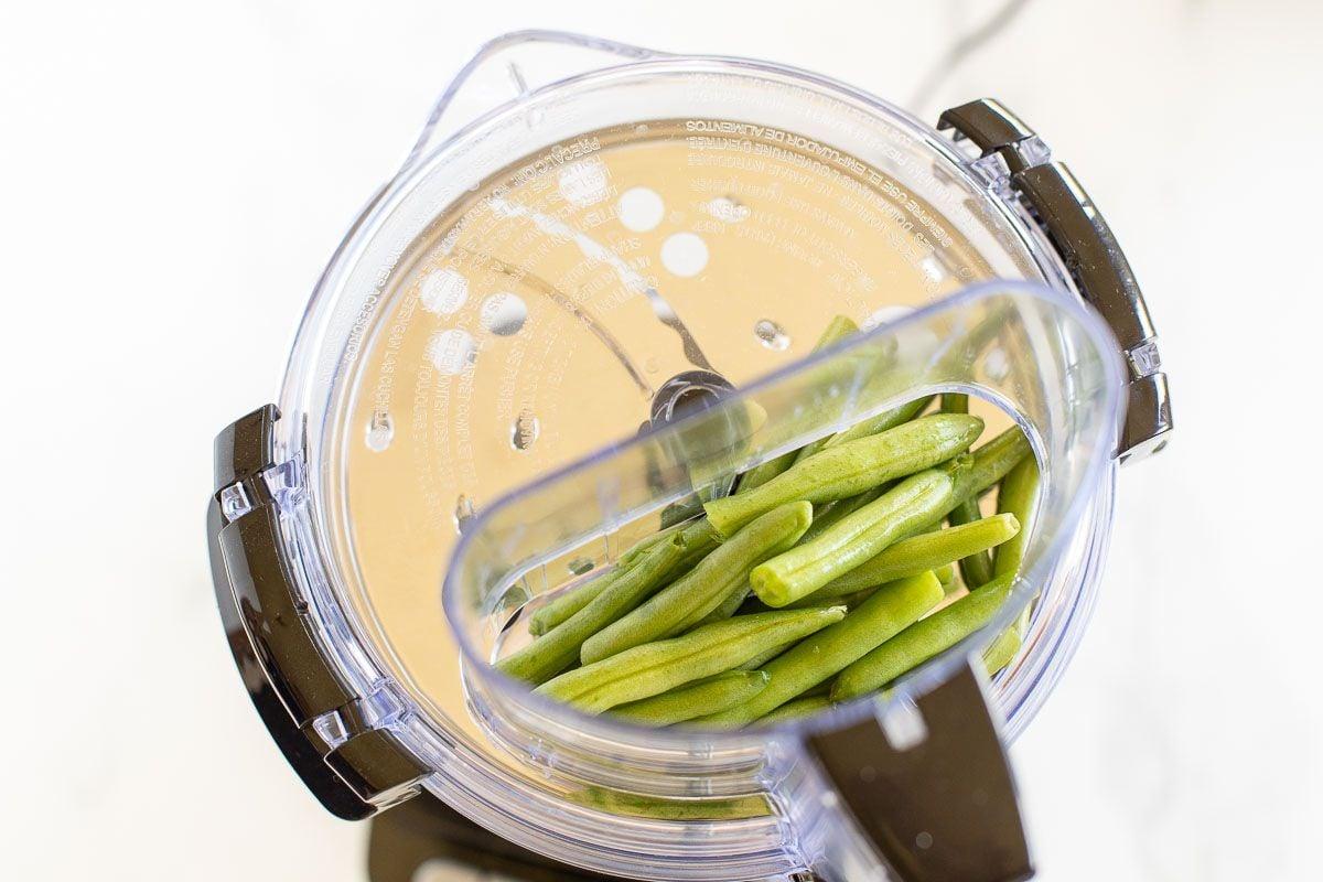 Fresh green beans inside a food processor.