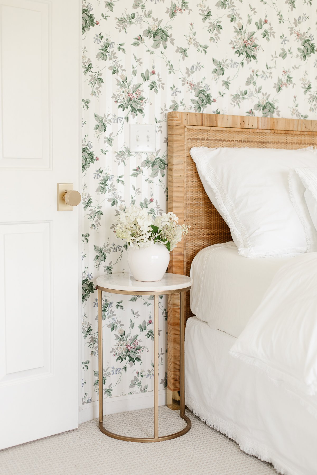 fresh cut limelight hydrangea blooms in a vase on a bedside table