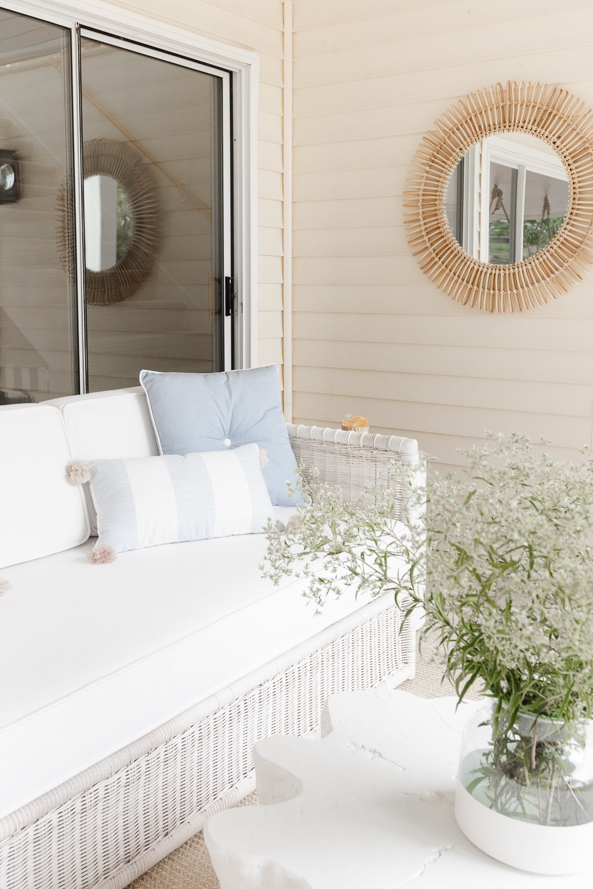 wicker sofa on covered patio with pillows flowers and mirror