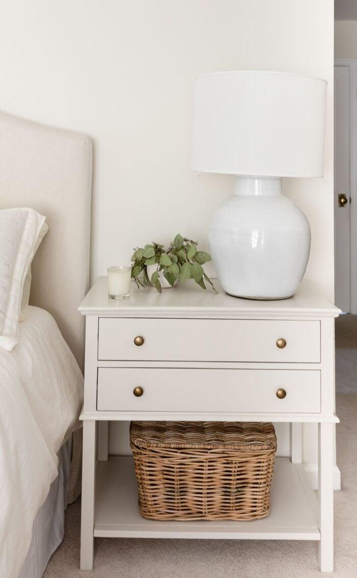 A nightstand in a cream bedroom, painted in Benjamin Moore Pale Oak paint color.