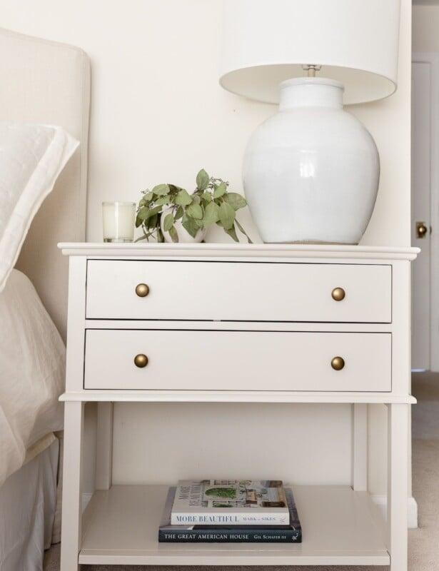 A nightstand in a cream bedroom, painted in Pale Oak Benjamin Moore paint color.