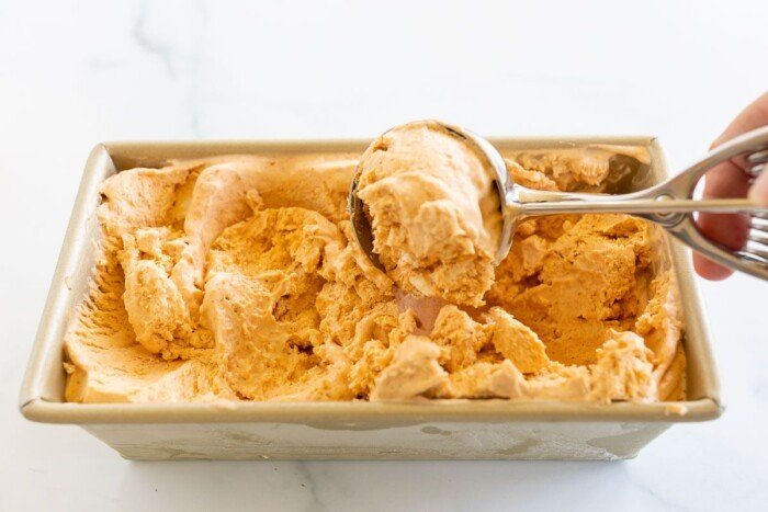 A gold loaf pan filled with pumpkin ice cream, scooper pulling a scoop out.