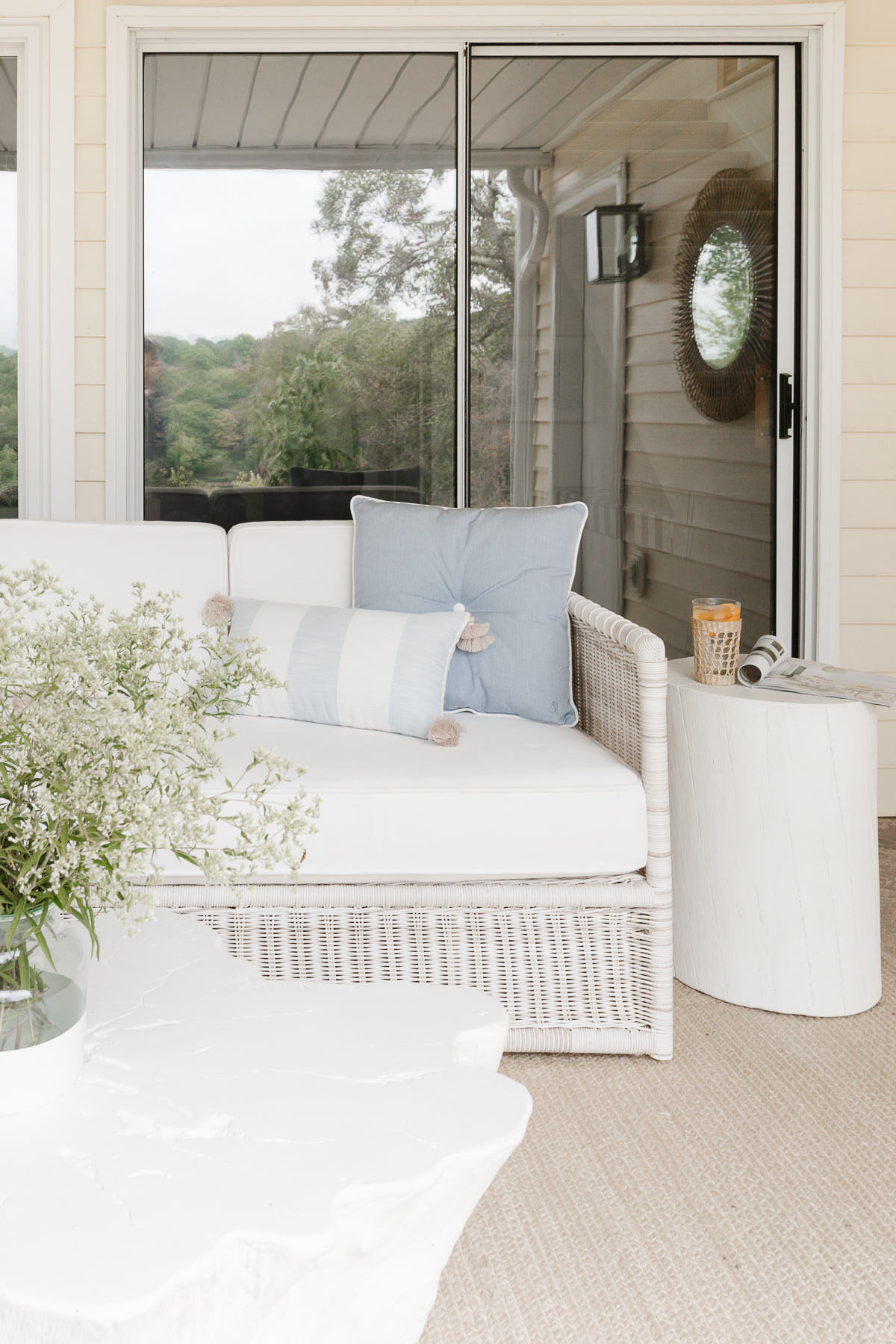 wicker sofa on covered patio with side and coffee tables