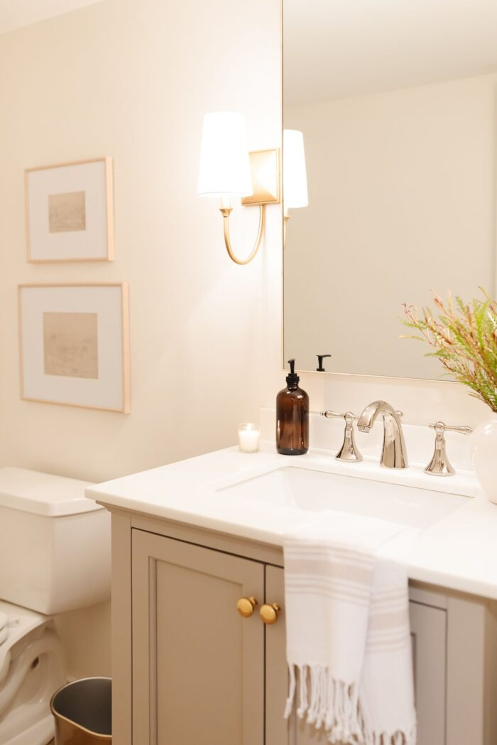 A basement bathroom with a greige painted vanity cabinet and gold sconces