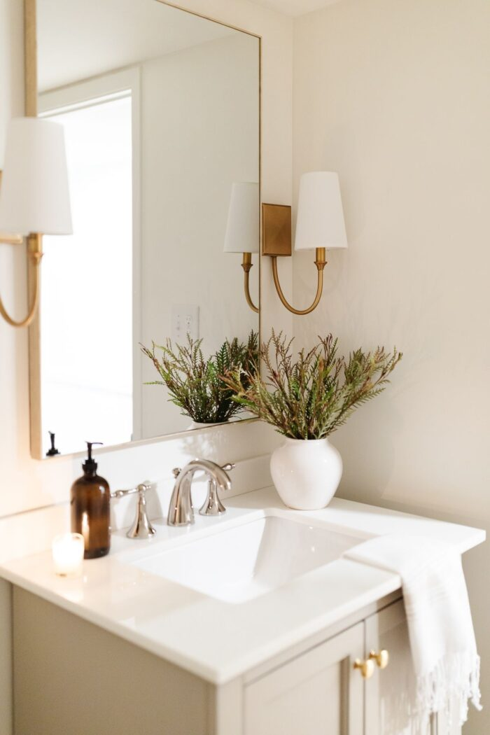 A bathroom in basement with gold sconces and a gray vanity