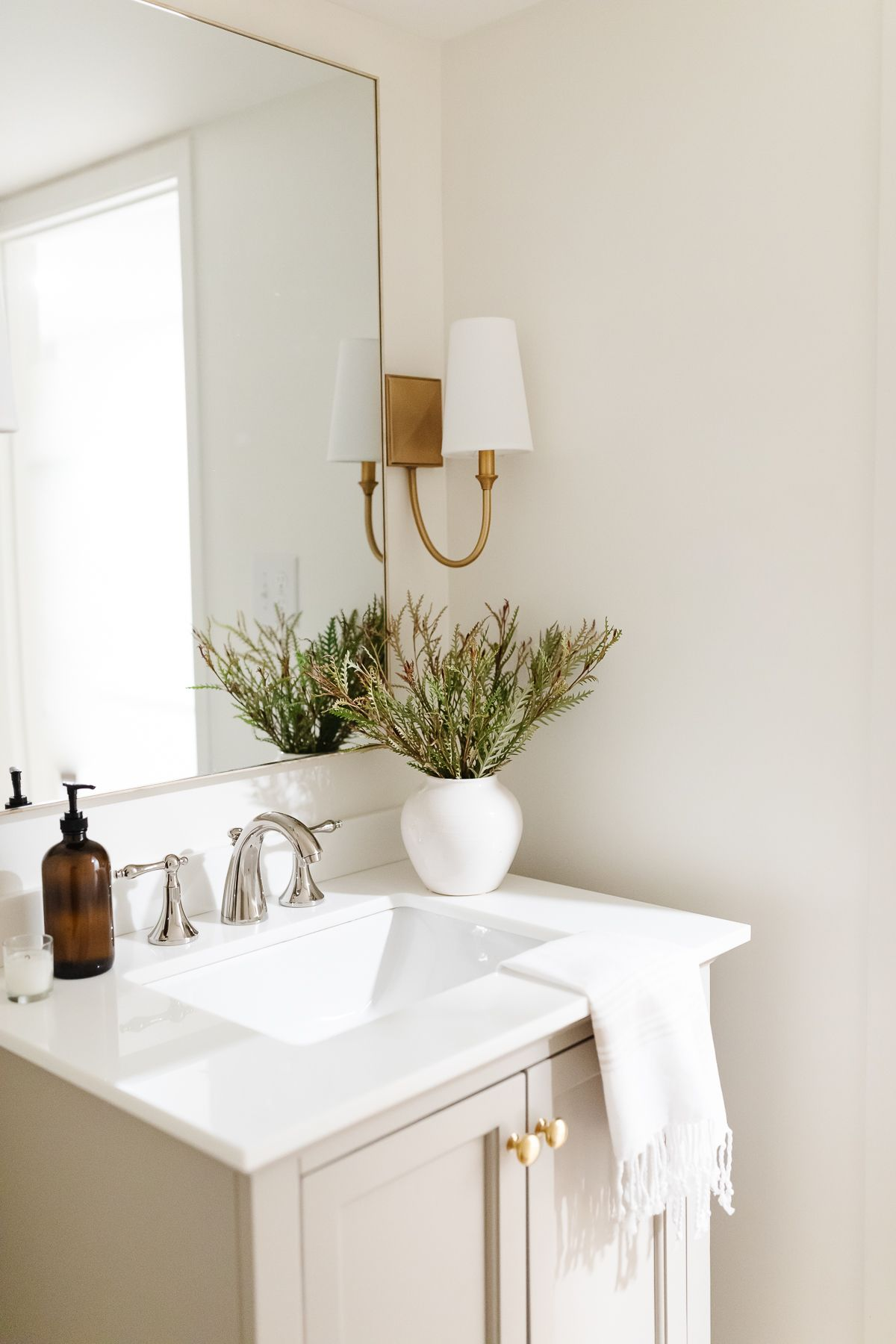 A small bathroom with gold sconces, greige vanity, and cloudy white painted walls