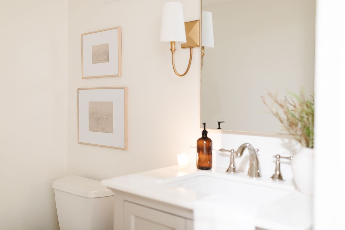 A small bathroom with gold sconces and white painted walls