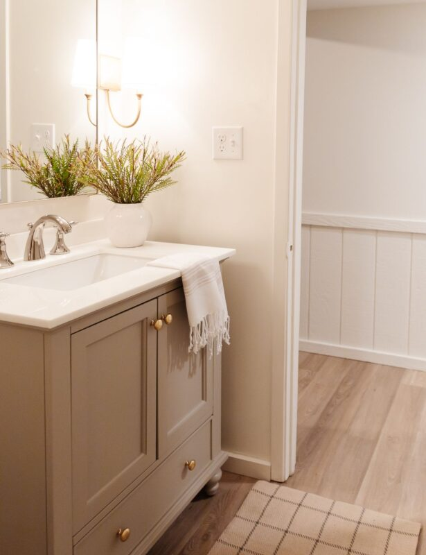 A small bathroom with gold sconces, greige vanity and walls painted Cloud White