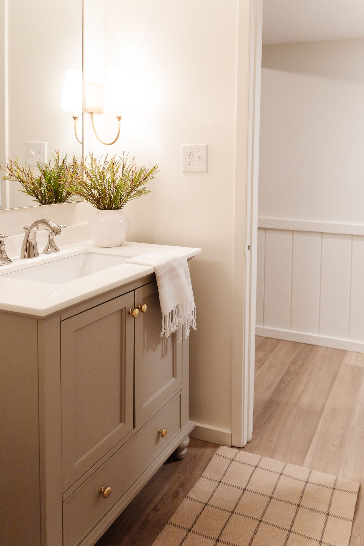 A small bathroom with gold sconces, greige vanity and cloudy white painted walls