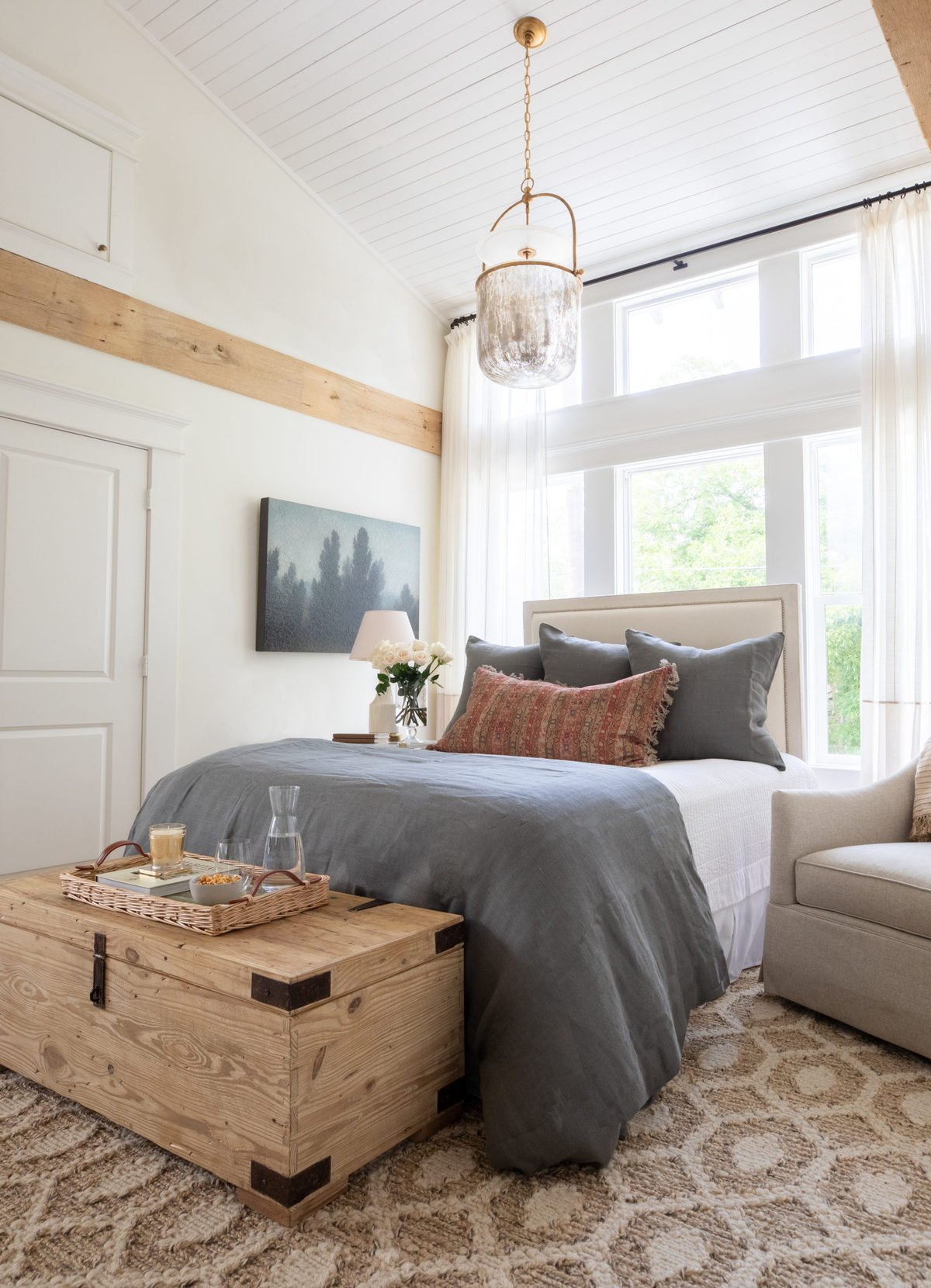 A guest room with white painted walls and wooden beams