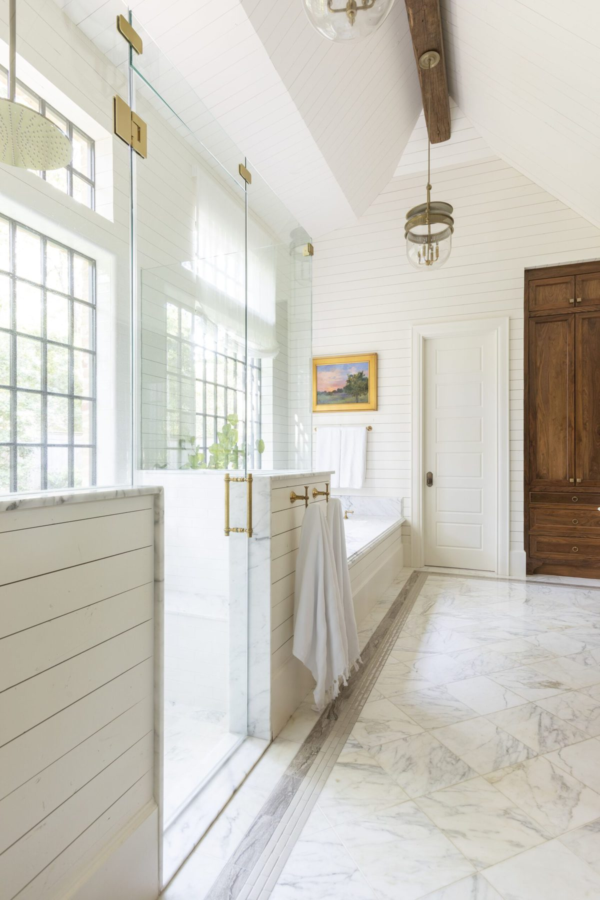 A primary bathroom with cloud white walls and a wooden door