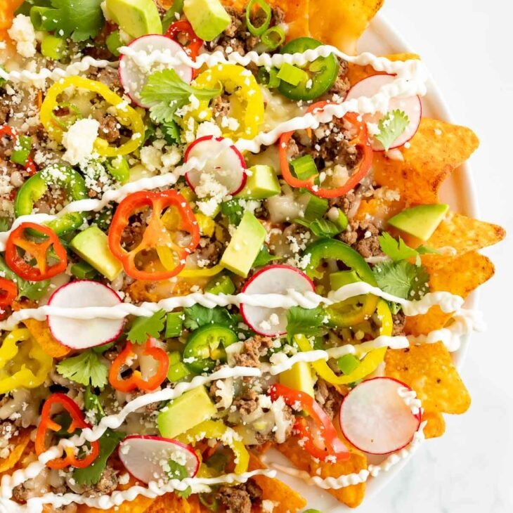 A plate full of a Doritos nachos recipe on a white surface.