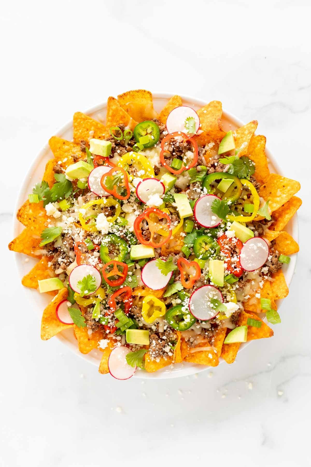 A white plate full of Doritos nachos, on a marble surface.