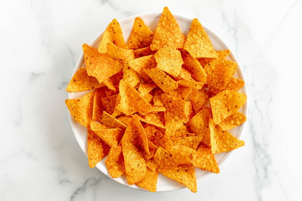 A white plate full of Doritos, on a marble surface.