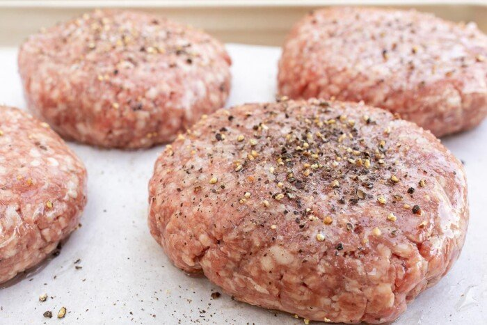 Homemade burger patties, uncooked, topped with seasoning on parchment paper.