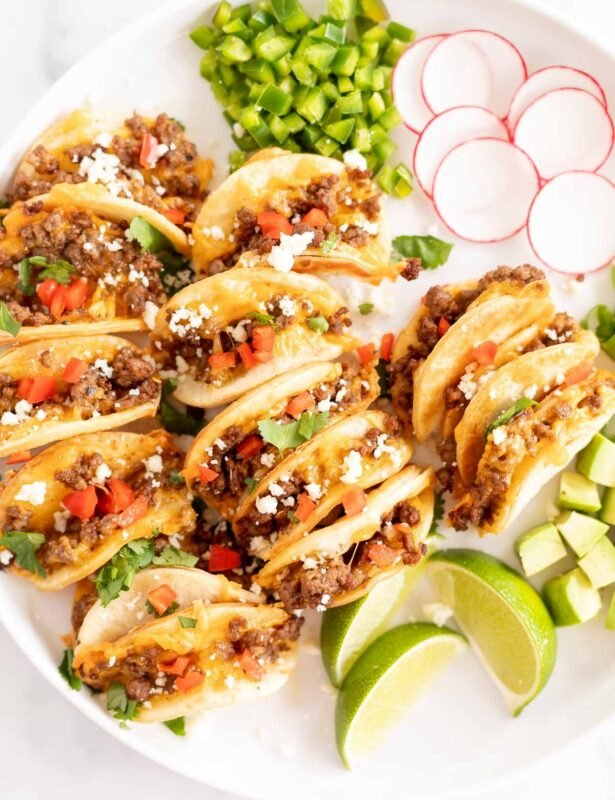 A white platter of mini tacos and toppings.