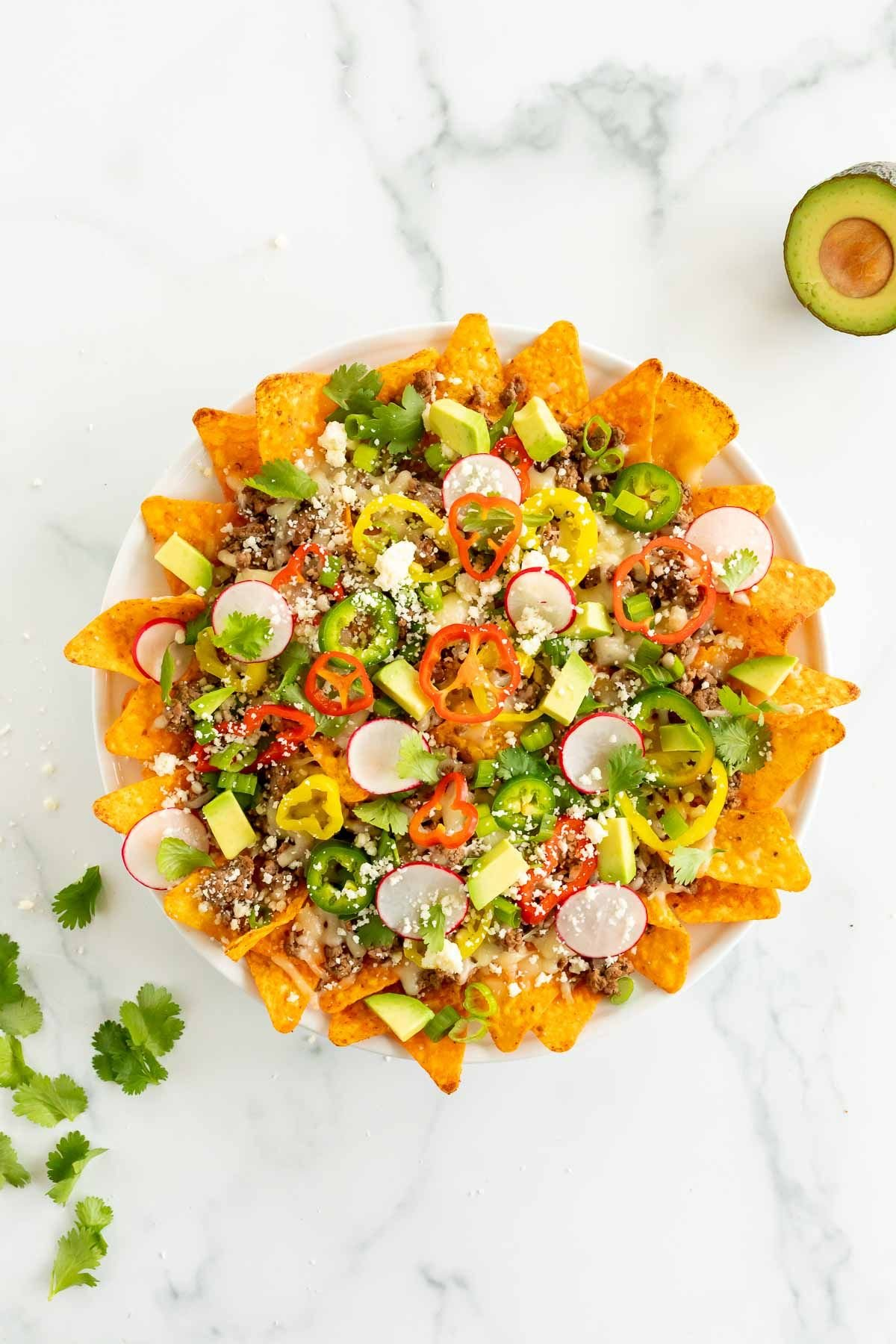 A white plate of nachos with Doritos, loaded with toppings